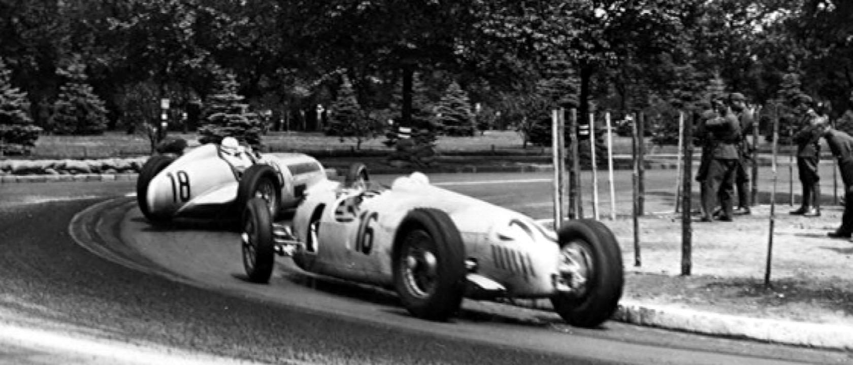 Rudolf Caracciola (br.18) u Mercedesu vodi ispred Bernda Rosemeyera (br.16) u Auto Unionu. Caracciola je odustao zbog kvara na motoru, a Rosemeyer je završio drugi, iza Nuvolarija u Alfa Romeu. (21.6.1936.) Foto: Bundesarchiv