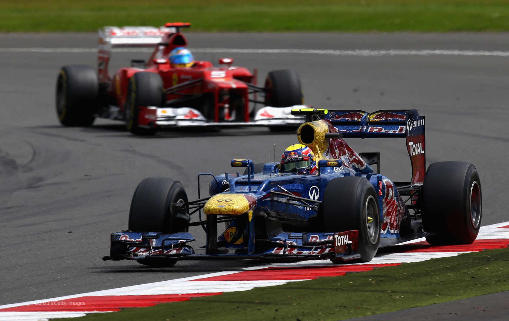 Mark Webber slavio je 2012. ispred Fernanda Alonsa nakon što ga je prestigao nekoliko krugova prije kraja. Red Bull je na toj utrci imao posebni vizualni identitet u čast humanitarne akcije Wings for Life. (8.7.2012.) Foto: Getty Images
